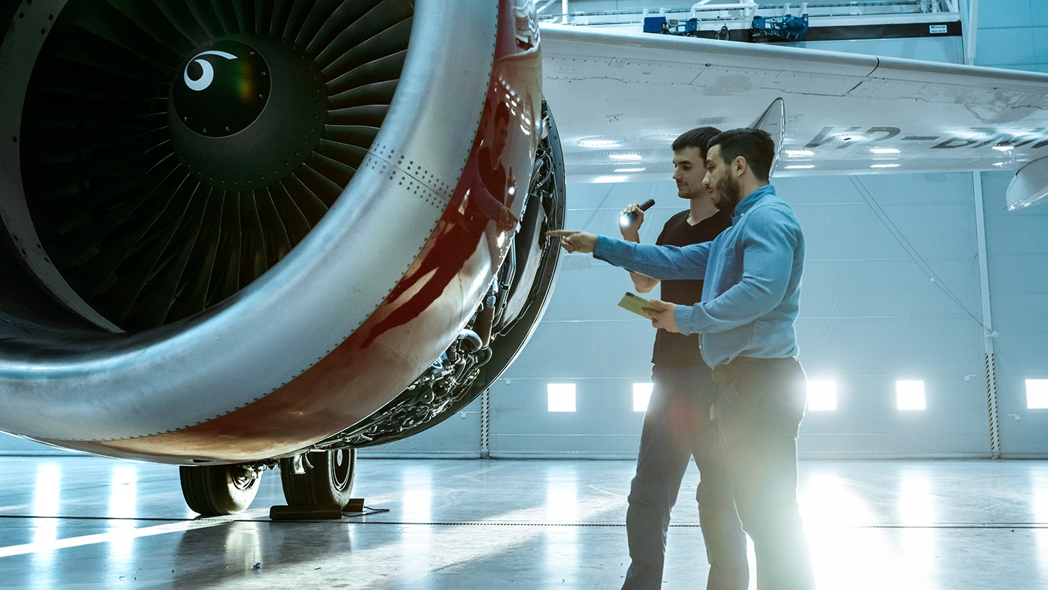 Two men in the Aerospace industry inspecting a plane